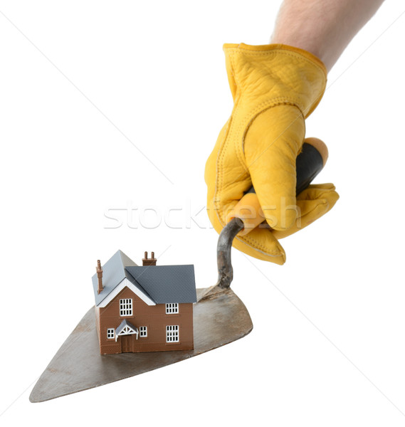 presenting a house on a trowel isolated on a white background Stock photo © hyrons