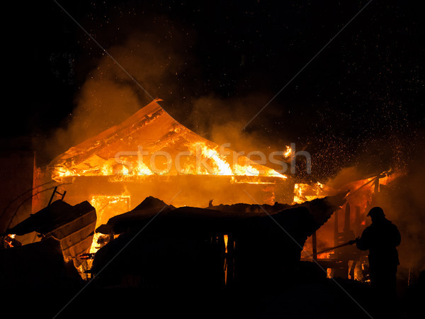 Firefighter at burning fire flame on wooden house roof Stock photo © ia_64