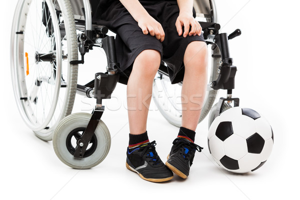 Disabled child boy sitting on wheelchair holding soccer ball Stock photo © ia_64