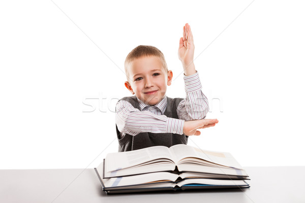 Child with books at desk gesturing hand up for answering school  Stock photo © ia_64