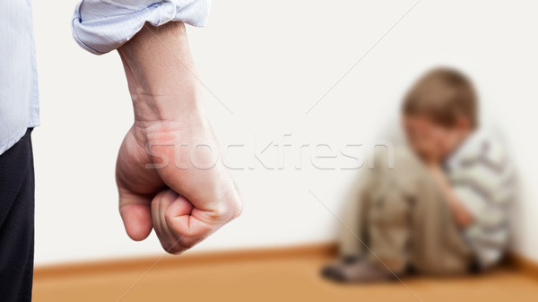 Angry man raised fist over wall corner sitting child boy Stock photo © ia_64