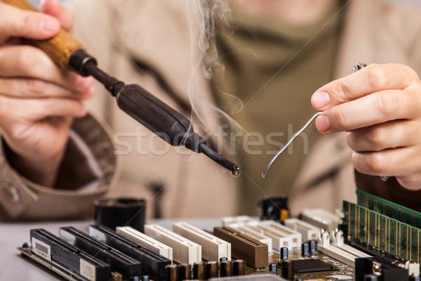 Emberi kéz tart forrasztás vasaló javít számítógép Stock fotó © ia_64