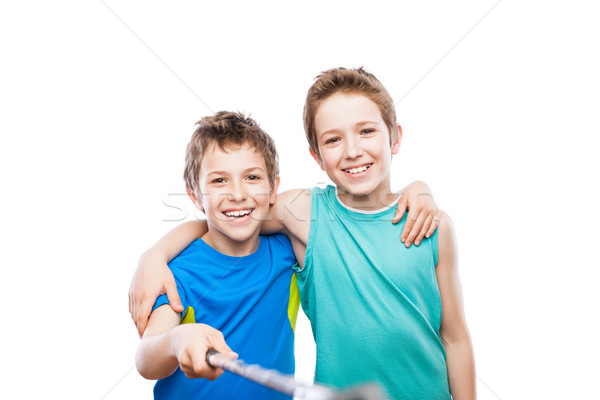 Two smiling child boy brothers holding mobile phone or smartphone selfie stick taking portrait photo Stock photo © ia_64