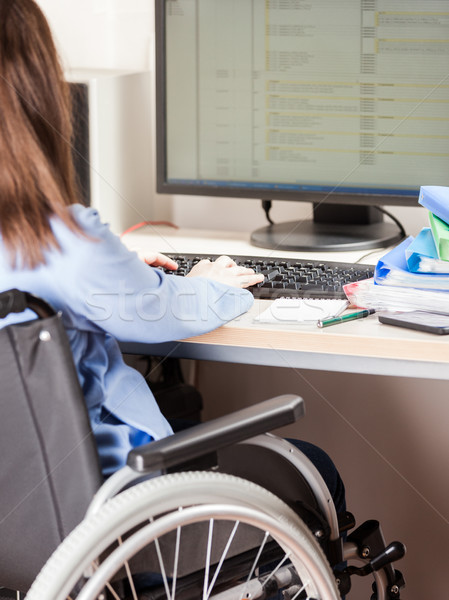 Invalid or disabled woman sitting wheelchair working office desk computer Stock photo © ia_64