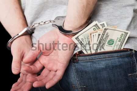 Handcuffs on hands hiding money Stock photo © ia_64