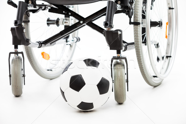Wheelchair for invalid or disabled person and soccer ball Stock photo © ia_64