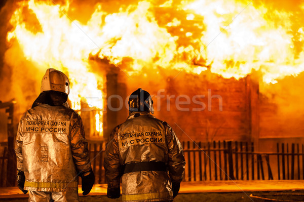 Firefighters at burning fire flame on wooden house roof Stock photo © ia_64