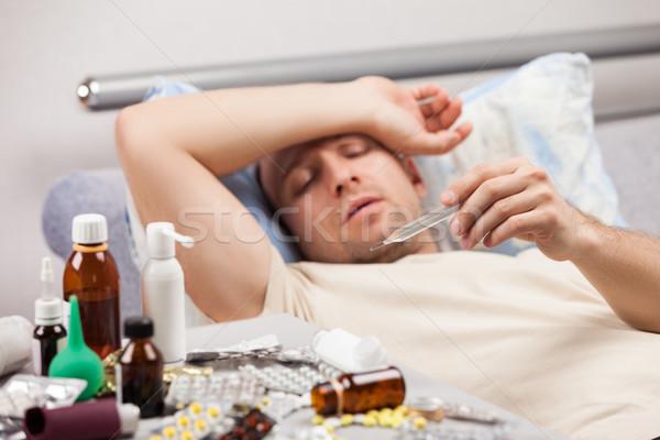 Indiszponált férfi beteg fekszik ágy felnőtt Stock fotó © ia_64
