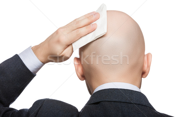 Hand holding tissue wiping or drying bald sweat head Stock photo © ia_64