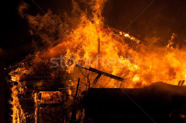 Stock photo: Burning fire flame on wooden house roof