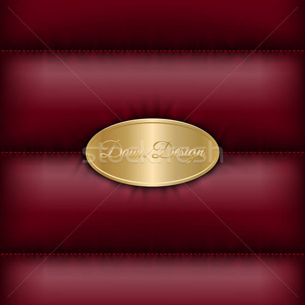 Stock photo: Winter quilted down jacket dark red background with golden oval shield for logo or text message