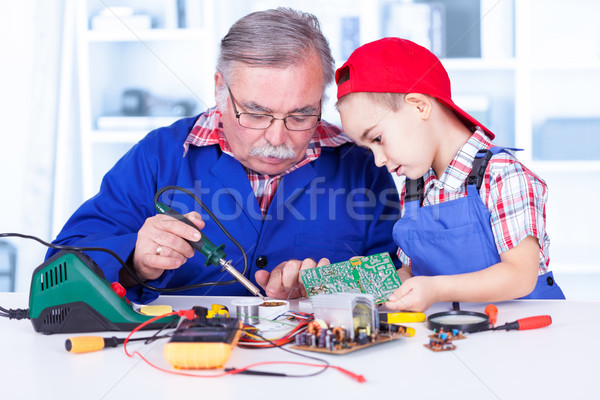 Grandfather explaining to grandchild how soldering works Stock photo © icefront