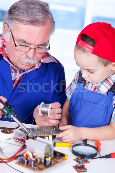 Grandfather showing PCB soldering to grandchild Stock photo © icefront