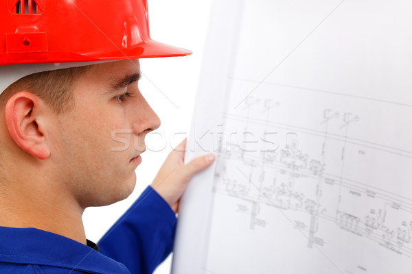 Young construction engineer surveying plans Stock photo © icefront