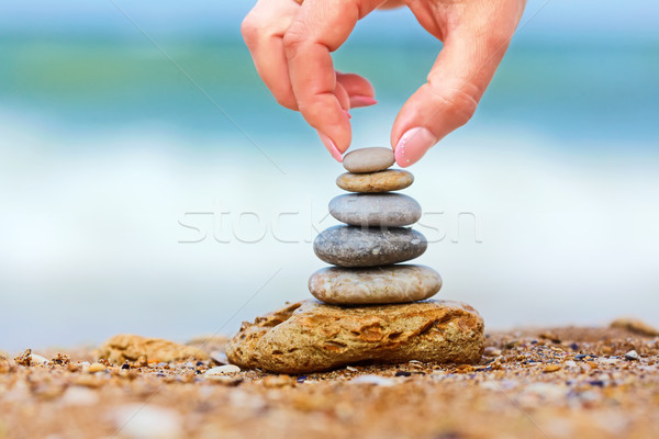 Hand placing the last pebble of a stacked tower Stock photo © icefront