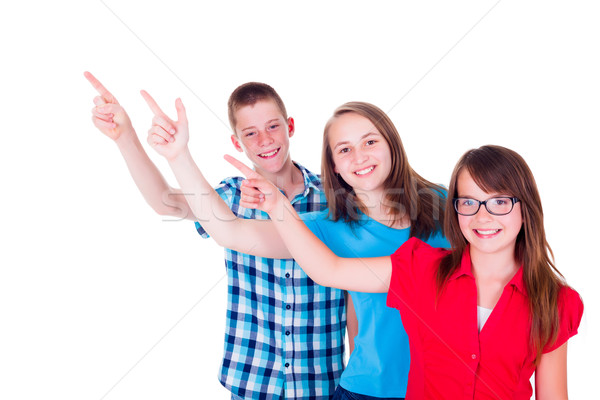 Happy teenagers pointing up to copy space Stock photo © icefront