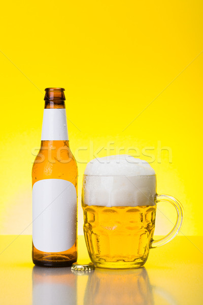 Mug with foamy beer and empty bottle Stock photo © icefront