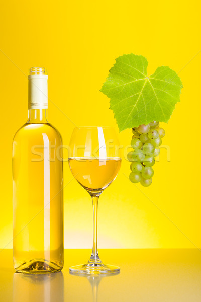 Stock photo: Bottle and glass of white wine with grape cluster