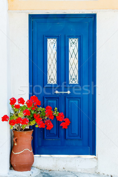 Greek house door in with geranium flowers Stock photo © icefront