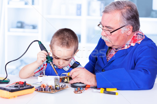 Grandfather teaching grandchild working with soldering iron Stock photo © icefront