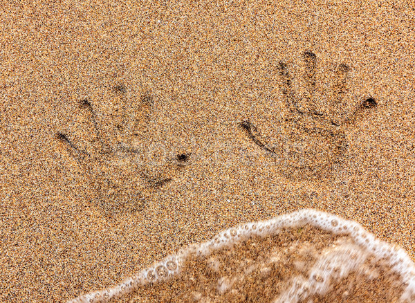 Handprint on sand being washed away Stock photo © icefront