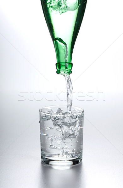 Stock photo: Water flowing from bottle into glass