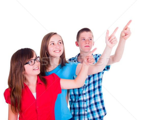 Teenagers pointing and looking up to copy space Stock photo © icefront