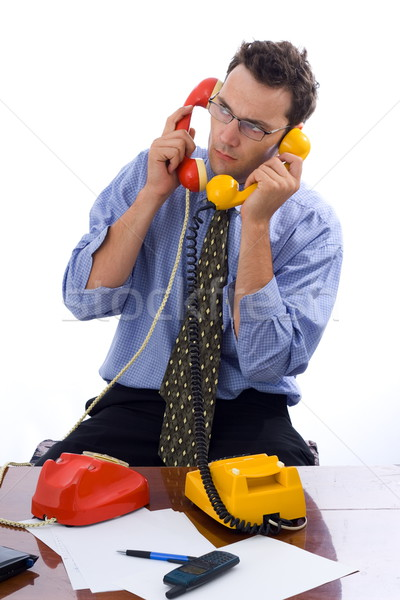 Talking on two telephones Stock photo © icefront