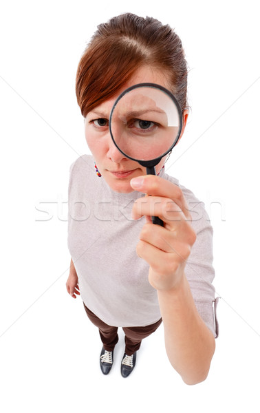 Serious woman as detective with magnifier Stock photo © icefront