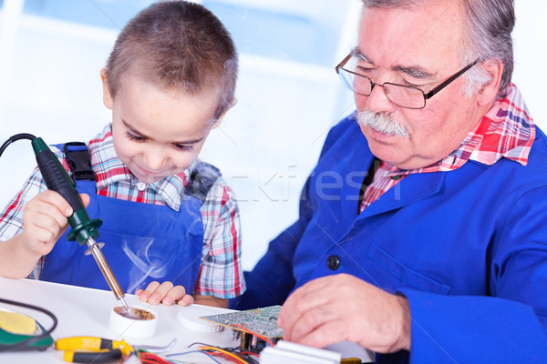 Grandfather teaching grandchild to use soldering resin Stock photo © icefront