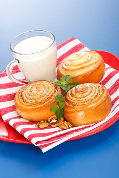 Three cinnamon rolls and jug of milk on red plate Stock photo © icefront