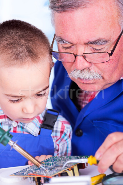 Grandfather teaching grandchild soldering with iron Stock photo © icefront