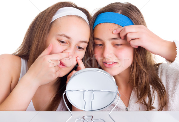 Girls searching for blemishes on theirs skin Stock photo © icefront