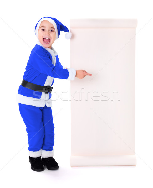 Little blue Santa Claus boy pointing at big wish list Stock photo © icefront