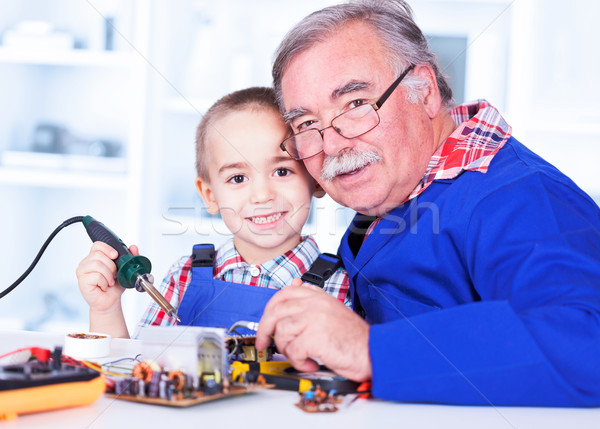 Happy grandfather and grandchild working together in workshop Stock photo © icefront