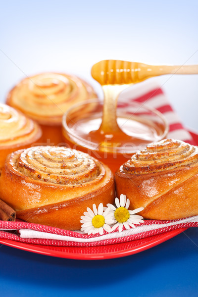 Pouring honey behind fresh cinnamon rolls Stock photo © icefront