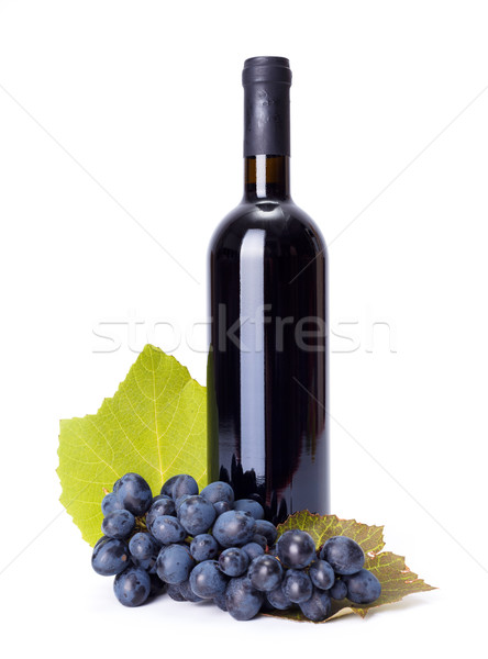 Bottle of red wine with blue grape cluster Stock photo © icefront