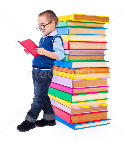 Stock photo: Little boy reading near big stack of books
