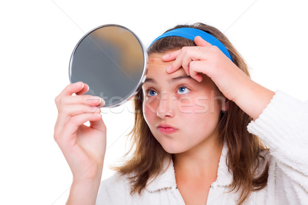Girl examine her pimples in the mirror Stock photo © icefront
