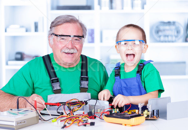 Happy grandfather and grandchild working in workshop Stock photo © icefront