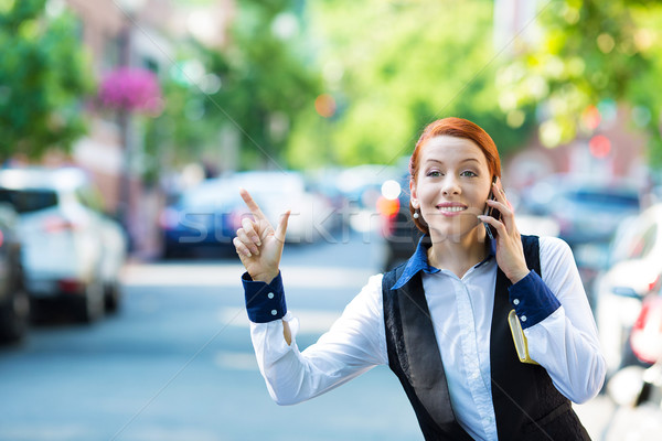 Young business woman talking on smart phone, hails taxi cab Stock photo © ichiosea