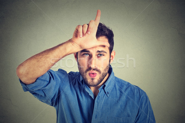 young man showing loser sign on forehead, looking at you with disgust Stock photo © ichiosea