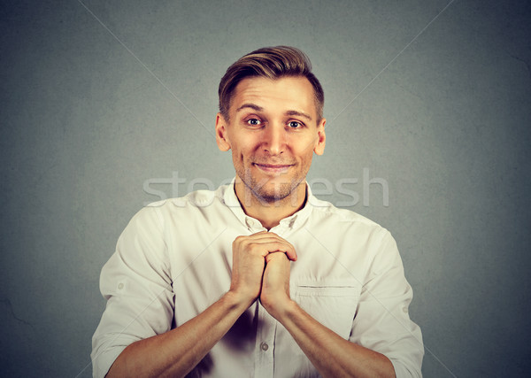 Kind young man showing clasped hands, pretty please  Stock photo © ichiosea