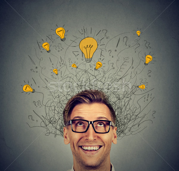 Excited man with many ideas light bulbs above head looking up  Stock photo © ichiosea