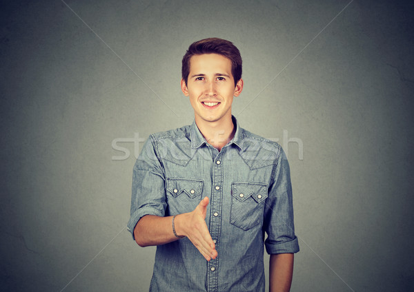 Casual joven ofrecimiento apretón de manos hombre aislado Foto stock © ichiosea