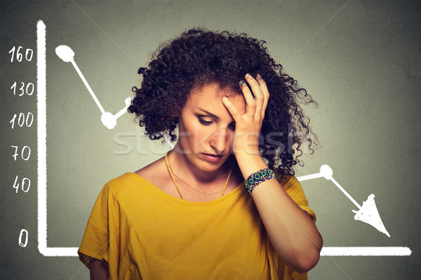 Stock photo: stressed sad business woman with financial market chart graphic going down