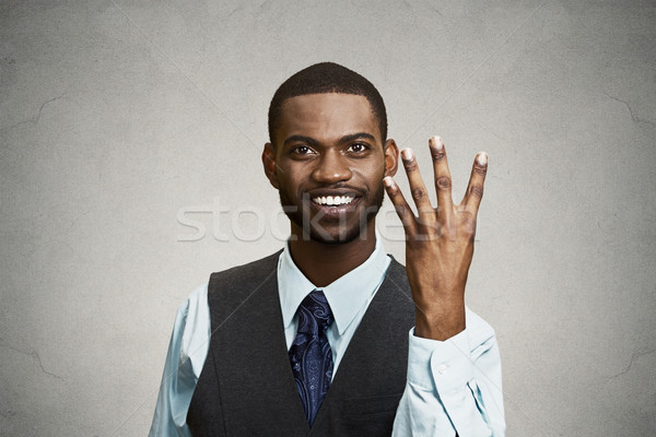 Smiling man giving four times gesture with hand Stock photo © ichiosea