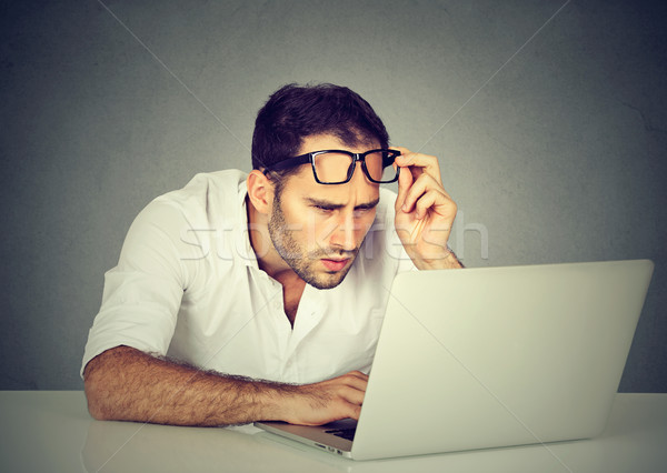 man with glasses having eyesight problems confused with laptop Stock photo © ichiosea