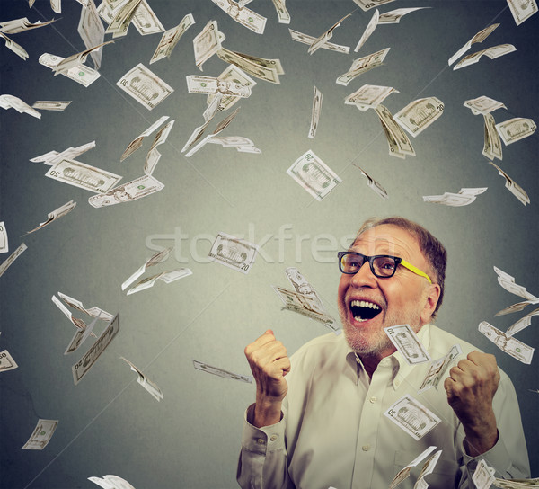 Senior man pumping fists ecstatic celebrates success screaming under money rain  Stock photo © ichiosea