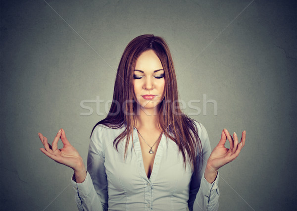 Stock photo: Woman meditating with eyes closed isolated on gray wall background